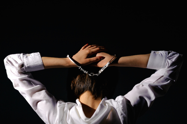 Isolated arrested handcuffed from neck girl in trouble on black background